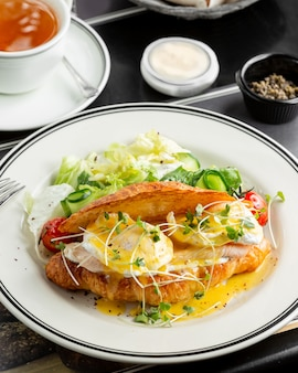 Croissant de salmão benedict com ovo poched, molho holandês e servido com salada fresca