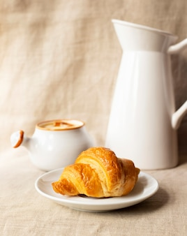 Croissant delicioso fresco. café da manhã com croissant, molho de caramelo e leite. fechar-se.