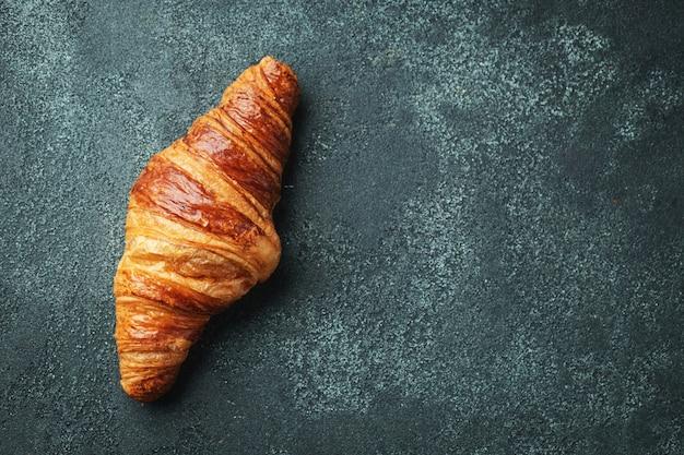Croissant doce fresco com manteiga no café da manhã.