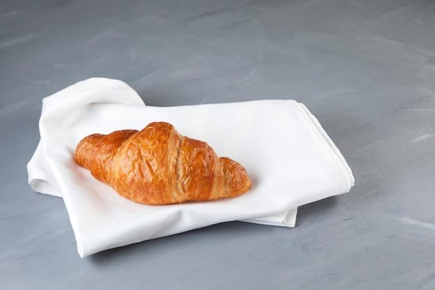 Croissant dourado fresco encontra-se em um guardanapo de linho branco.