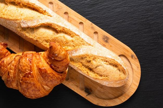 Croissant e baguete francesa na placa de ardósia preta com espaço de cópia