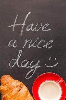 Croissant e café com mensagem de manhã
