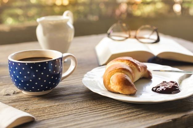 Croissant e café em uma mesa de madeira