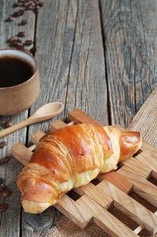 Croissant e café na velha mesa de madeira com espaço de cópia