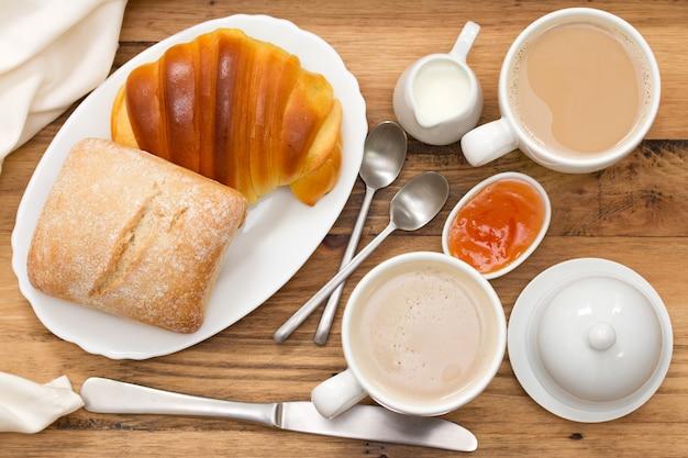 Croissant e pão com café em madeira marrom