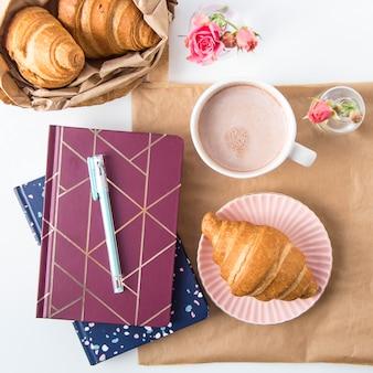 Croissant e uma xícara de cacau em uma área de trabalho branca ao lado de blocos de anotações. conceito de quebra. vista superior, lay plana
