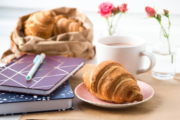 Croissant e uma xícara de cacau em uma área de trabalho branca ao lado de blocos de anotações. conceito de quebra