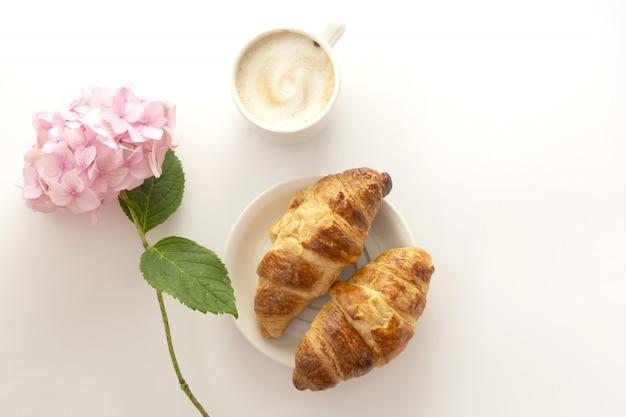 Croissant e uma xícara de café com hortênsia rosa. copie o espaço.