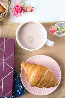 Croissant e uma xícara de chocolate em uma área de trabalho branca ao lado de blocos de anotações