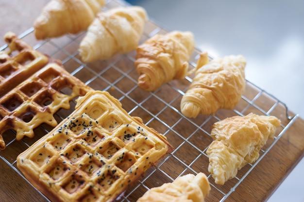 Croissant e waffle refrigerando na malha de arame