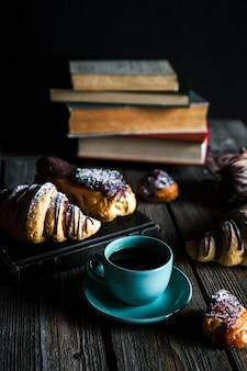 Croissant e xícara de café preto branco sobre tela marrom.