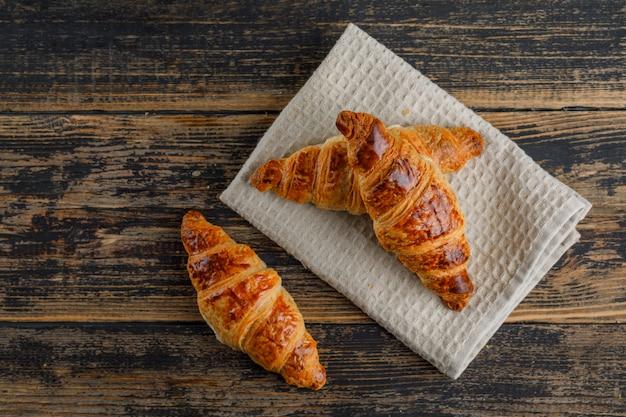 Croissant em madeira e toalha de cozinha. configuração plana.