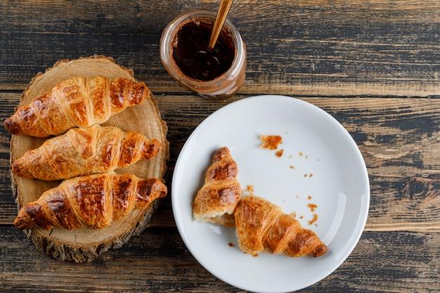Croissant em um prato com creme de chocolate plano leigos na tábua de madeira e