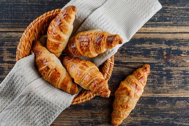 Croissant em uma cesta com pano sobre uma mesa de madeira. configuração plana.