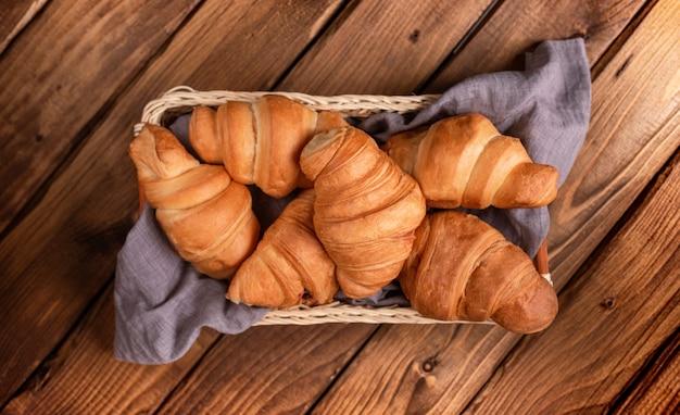 Croissant em uma cesta em um guardanapo cinza-azulado sobre uma mesa de madeira.