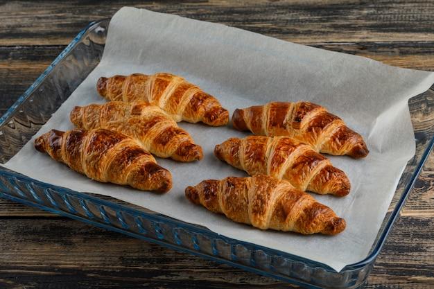 Croissant em uma placa de vidro alto ângulo vista sobre uma mesa de madeira
