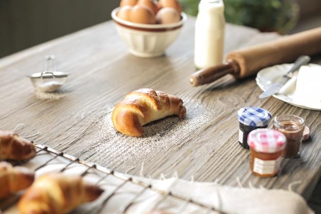 Croissant feitos à mão e ingredientes para fazê-lo em uma mesa de madeira