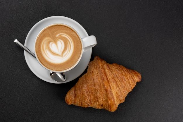 Croissant francês clássico e xícara de café com cappuccino e latte art com padrão de coração
