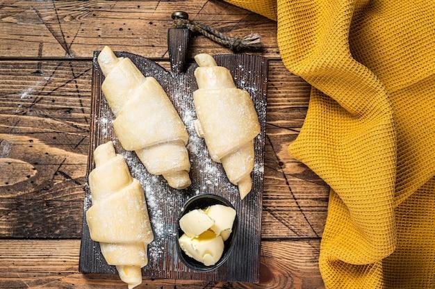 Croissant francês cru e cru em uma tábua de madeira