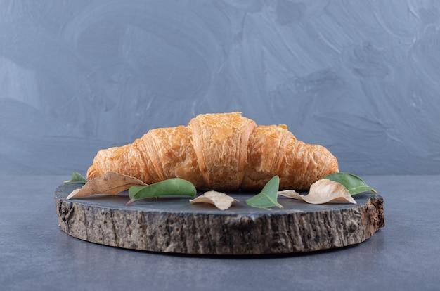 Croissant francês fresco na placa de madeira sobre fundo cinza.