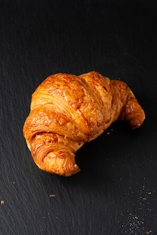 Croissant francês na placa de ardósia preta com espaço de cópia