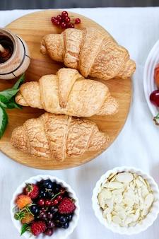 Croissant francês tradicional em fundo de mesa branca, saboroso café da manhã com croissants, padaria fresca, vista de cima