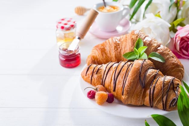 Croissant fresco com frutas e geléia no café da manhã, isolado no fundo branco de madeira