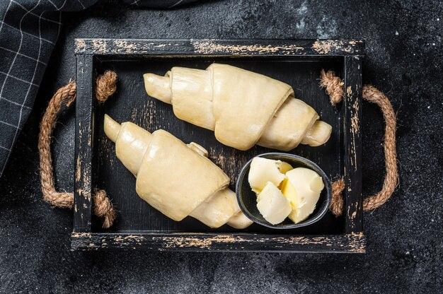 Croissant fresco cru em uma bandeja de madeira. fundo preto. vista do topo.