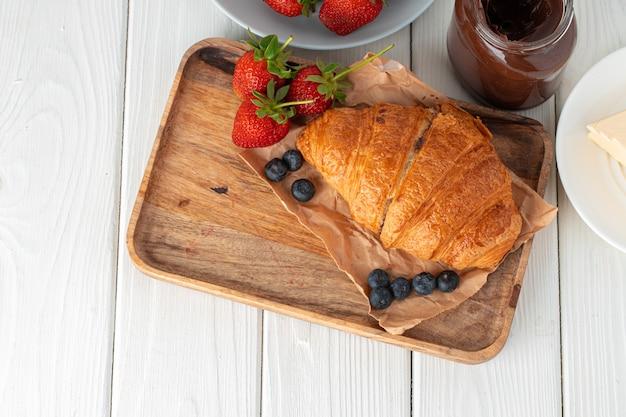 Croissant fresco decorado com frutas na placa de madeira branca
