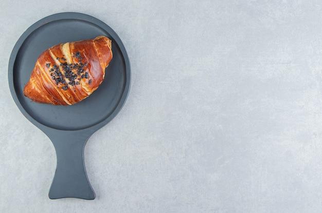 Croissant fresco decorado com gota de chocolate no quadro negro.