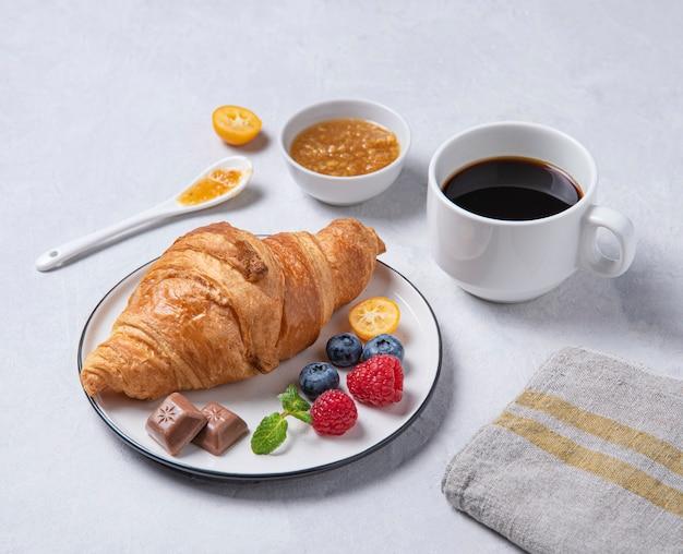 Croissant fresco em um prato branco com geléia de kumquat, mirtilos e framboesas com uma xícara de café vegan em um fundo branco.