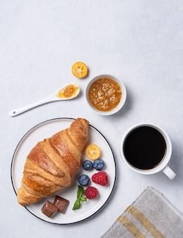 Croissant fresco em um prato branco com geléia de kumquat, mirtilos e framboesas com uma xícara de café vegan em um fundo cinza.