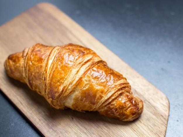 Croissant fresco na tábua de madeira