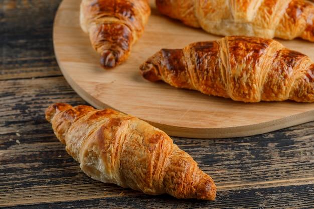 Croissant na placa de madeira e de corte, close-up.