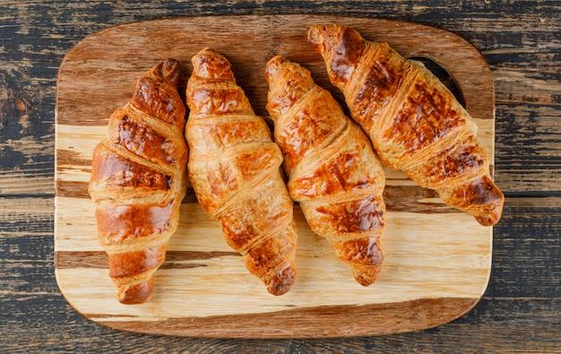 Croissant na tábua de madeira e corte. configuração plana.