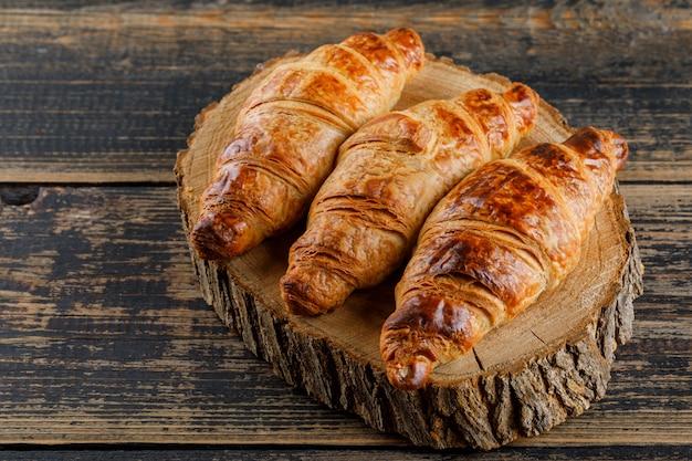 Croissant na tábua de madeira e corte. vista de alto ângulo.