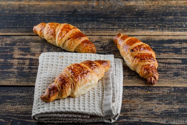 Croissant na toalha de madeira e de cozinha, opinião de ângulo alto.