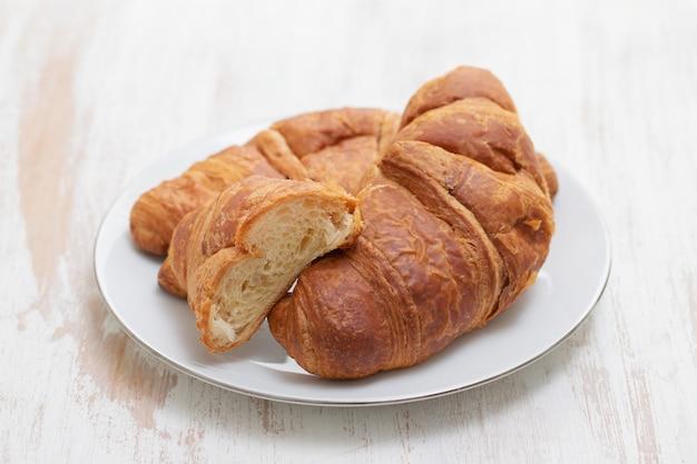 Croissant no prato branco na superfície de madeira branca