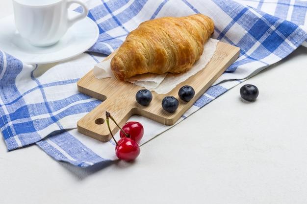 Croissant num guardanapo xadrez branco e azul. xícara de café, cereja e mirtilos na mesa.