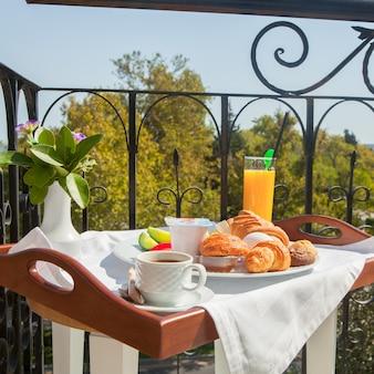 Croissant, ovo cozido, café da manhã suco de laranja na bandeja na varanda