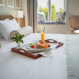 Croissant, ovo cozido, suco de laranja, iogurte, café da manhã na bandeja na cama no quarto de hotel