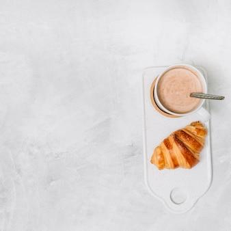 Croissant perto de copo de bebida na placa de corte