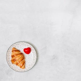 Croissant perto de coração de ornamento na placa