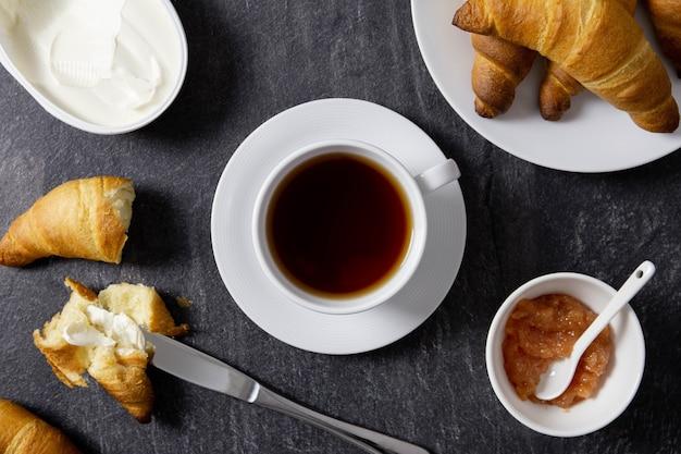 Croissant recém-assado com geleia, cream cheese e chá preto no café da manhã no escuro.