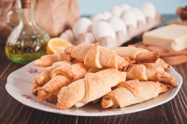 Croissant recém-assado no prato com ingredientes e utensílios de cozinha na mesa de madeira