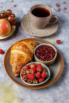 Croissants acabados de fazer com compota de framboesa e frutos de framboesa.