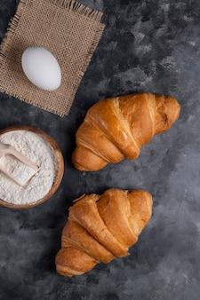 Croissants acabados de fazer com ovos de galinha e tigela de madeira com farinha.