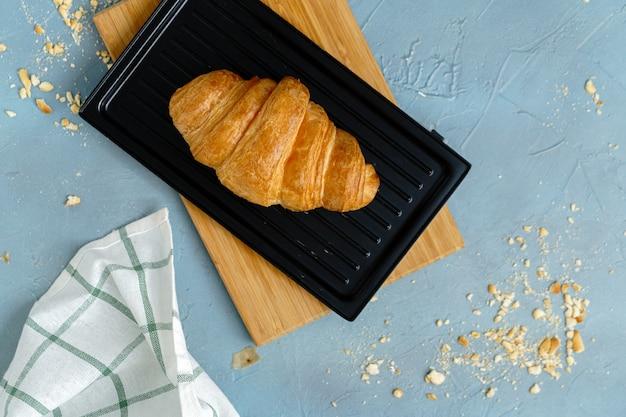 Croissants acabados de fazer na placa preta. croissants franceses e americanos e bolos assados são apreciados no mundo todo.