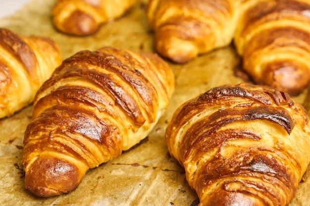 Croissants amanteigados deliciosos removidos do forno em uma assadeira. conceito de pastelaria caseira. café da manhã tradicional italiano ou francês