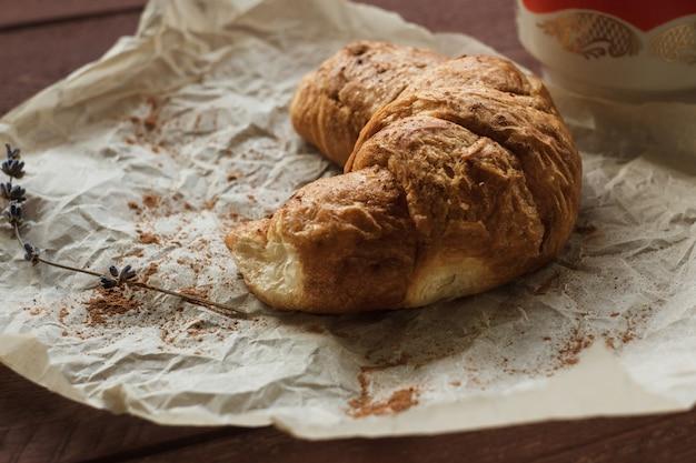 Croissants amanteigados saborosos na tabela de madeira velha.